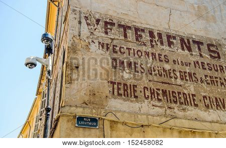 AIX-EN-PROVENCE FRANCE - JUL 17 2014: Old inscription on building of a store selling clothes with the street name Rue Lieutad and two security camera surveilling the city