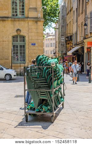 AIX-EN-PROVENCE FRANCE - JUL 17 2014: Man moving cafe chairs in the central Place of Aix-En-Provence - getting ready for the busy evening in the city
