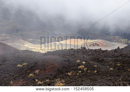 Southern flank of Mount Etna an active stratovolcano on the east coast of Sicily Italy showing lava flows from eruption and new vegetation on the lava fieldat elevation of aproximtely 1900m with low hanging clouds.