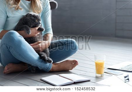 My baby. Close up of barefoot woman sitting on wooden floor and holding grey cat.