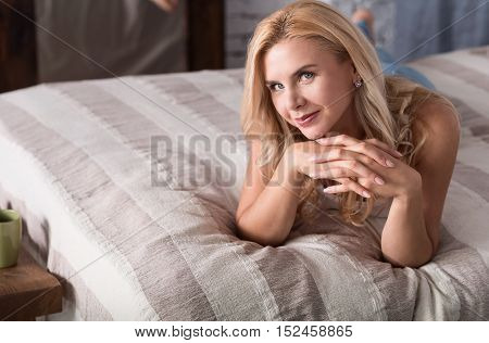 Linking in. Pretty blond-haired woman lying on soft bed and intently looking forward.