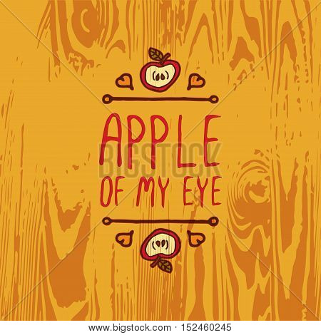 Hand-sketched typographic element with apple, hearts and text on wooden background. Apple of my eye