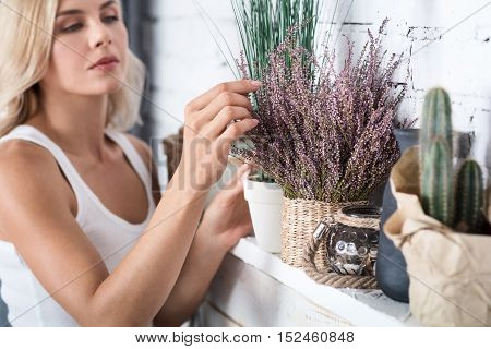 Fixing imperfections. Young blond woman standing near decorated shelf and ordering fake flowers.