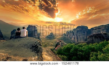 Couple enjoys the breathtaking view of Meteora Roussanou Monastery at sunset, Greece