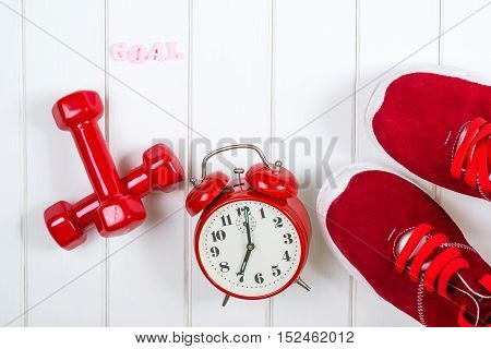 Red sneakers clock and dumbbells on the wooden backgroyund.