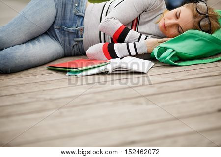 Sleeping student with Tablet and notebooks outdoors