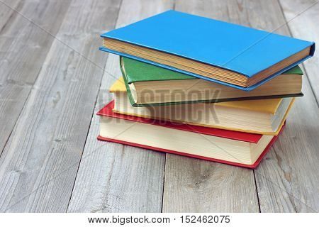 Pile of books with color covers on a wooden table. Education back to school.