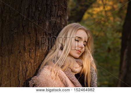 happy blond girl with closed eyes near tree, toned image