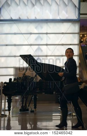 LOS ANGELES, UNITED STATES - DECEMBER 28: An Asian traveler young woman passes a piano of the Centurion Lounge and cocktail bar at LAX airport on December 28, 2015 in Los Angeles.
