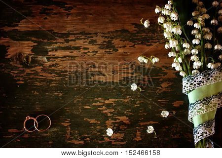 old shabby wooden painted background and a beautiful bouquet of fresh white flowers lily of the valley