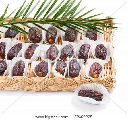 Dried date palm fruits with green leaf isolated on white background.