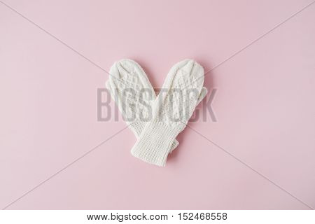 beauty white feminine knitted mittens on pink background. flat lay top view