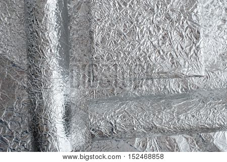 Silver foil figures with shiny crumpled surface. Contemporary art