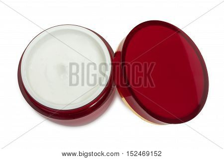 Red glossy round box container and cover with cosmetic cream. Isolated on a white background close-up top view.