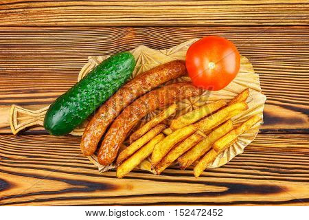 Homemade fast food portion of french fries grilled sausages tomato cucumber on wooden board
