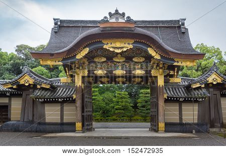 Kyoto Japan - September 19 2016: Majestic Kara-mon gate at the Nijo Castle. Plenty of gold trimmings and colorful woodwork. Cloudy sky and green foliage in background.