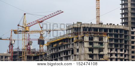 View of built high-rise buildings and construction cranes concept