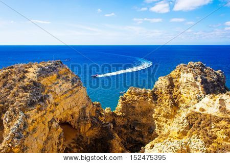 beautiful ocean view with motorboat and cliffs Algarve region Portugal
