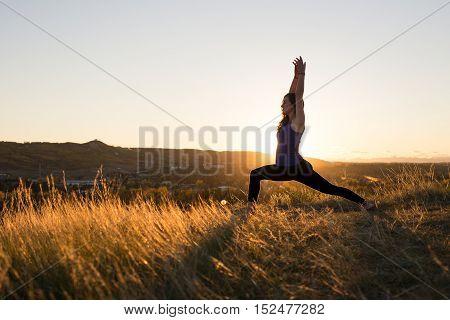 Woman doing yoga warrior I pose during evening sunset