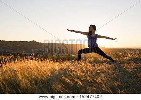 Woman doing yoga warrior II pose during evening sunset