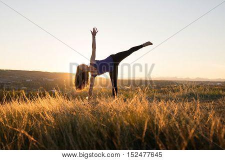 Woman doing yoga half moon pose during evening sunset
