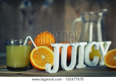 Delicious fresh orange juice on a wooden textural background