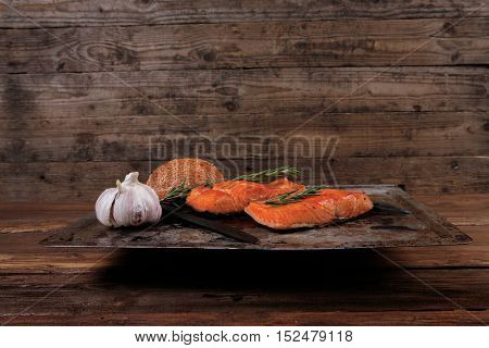delicious portion of raw fresh salmon fillet with aromatic herbs and spices on vintage tray over wooden table - healthy food, diet cooking concept with background space