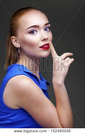 Woman requires silence. Young beautiful blonde woman has put forefinger to lips as sign of silence