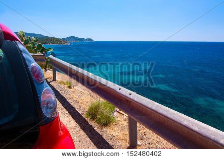 A part of a red car parked near the view point on the sea in Cala Regina. Location closed to Cagliari Sardinia Italy.