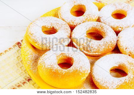 Icing homemade donuts on yellow plate. Sweet dessert pastry doughnuts. Hanukkah sweet donuts.