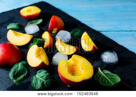 Slices of nectarines and peaches on blue wooden background. Fresh fruit background. Healthy eating concept with nectarines and peaches. Selective focus.