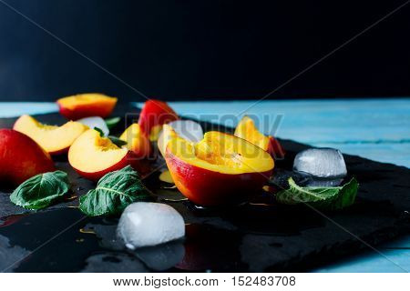Slices of ripe nectarines and peaches on black stone background. Fresh fruit background. Nectarines and peaches as healthy eating concept. Selective focus.