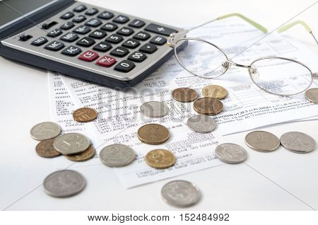 On the paid receipts are glasses calculator and small coins