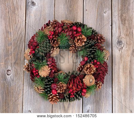 Holiday evergreen and berry wreath on top of rustic wood