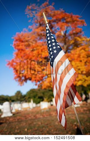 American veteran flag in autumn cemetery. Tombstones, a tree and blue sky background.