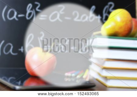 blurred educational concept in the photos as a pile of books and a fresh apple as a source of vitamins for study