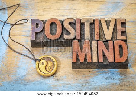Positive mind  word abstract in vintage letterpress wood type with a yin and yang pendant