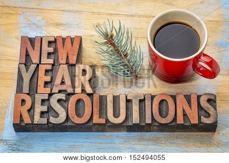 New Year resolutions - word abstract in vintage letterpress wood type with a cup of coffee and a twig of silver spruce