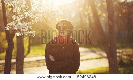 Slender girl in sunglasses posing in the park against the backdrop of cherry blossoms. The setting sun illuminates the hair from behind.