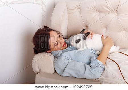 Cute girl with a rabbit in his arms. She lies with him on the couch. Pets. Love to the animals. Funny animals.