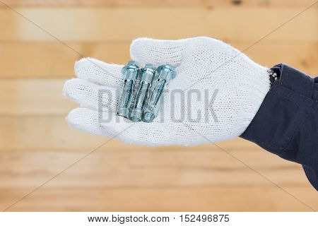Hand In Glove Holding Metal Anchor Bolts