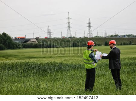 White worker in protective clothing and an orange helmet on workplace