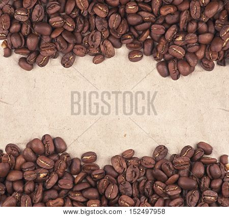 Roasted coffee beans on kraft paper as background with a place for an inscription