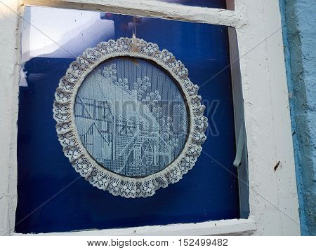 Traditional European handmade crochet lace decoration shaped as a circle in a window