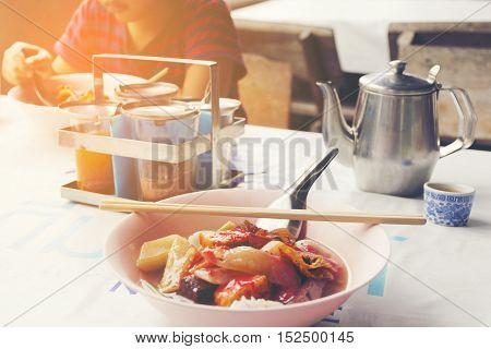 Roadside restaurant of Asia with Thai noodles and background of boy eating his noodle on table.1