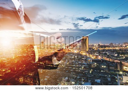 Double Exposure Businessman Working on Digital Tablet Outdoor, and city view background