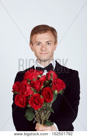 Handsome Groom holding red roses