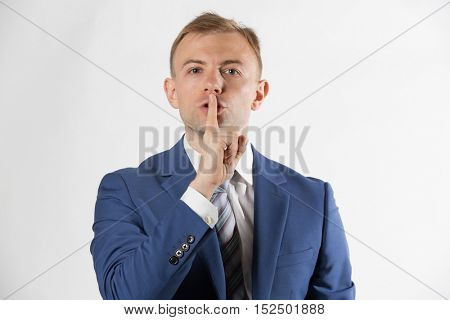 Businessman with finger over lips