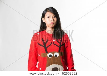 Portrait of woman in Christmas sweater standing making funny face over gray background