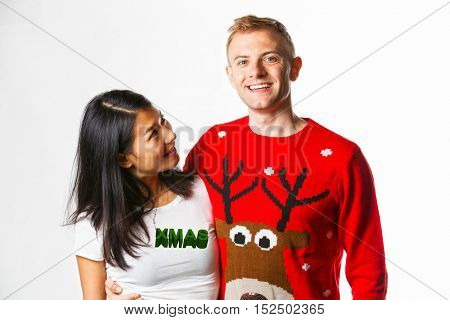 Portrait of happy multi ethnic couple wearing christmas jumpers in studio whilst looking at each other